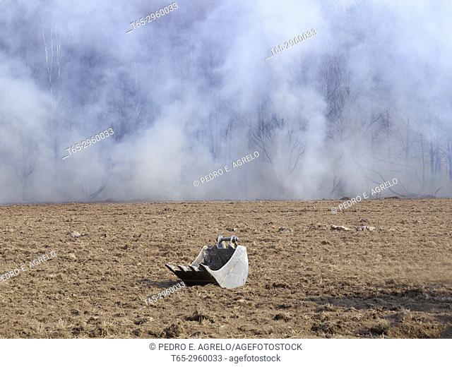 The bucket of a shovel spade in a field of earth, and in the background smoke in a forest in an uncontrolled wildfire in Galicia, Lugo. Galicia, Spain
