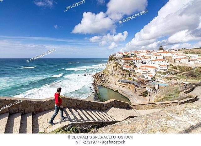 Tourist admires the perched village of Azenhas do Mar surrounded by the blue water of the Atlantic Ocean Sintra Portugal Europe
