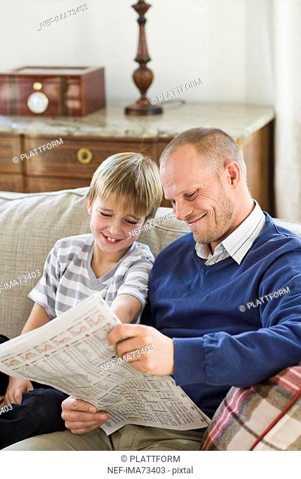 Father and son reading the newspaper, Sweden