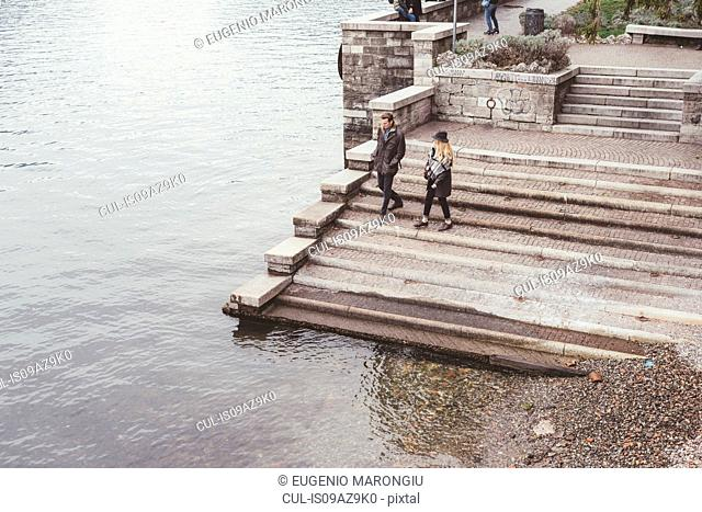 High angle view of young couple strolling down harbour stairs, Lake Como, Italy