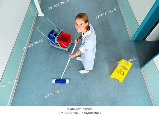 High Angle View Of Janitor With Mop Cleaning Floor Of Corridor Pass
