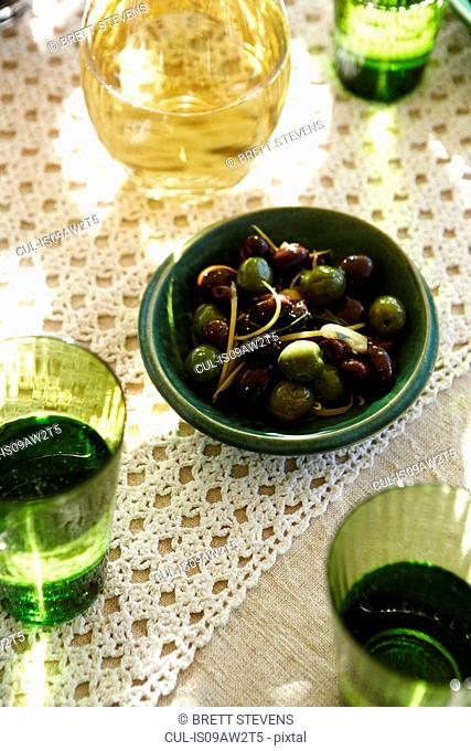 Overhead view of warmed olives in bowl with white wine and water