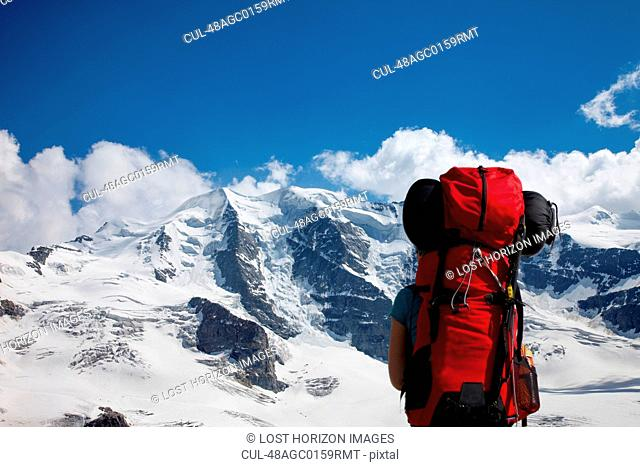 Backpacker admiring snowy mountains