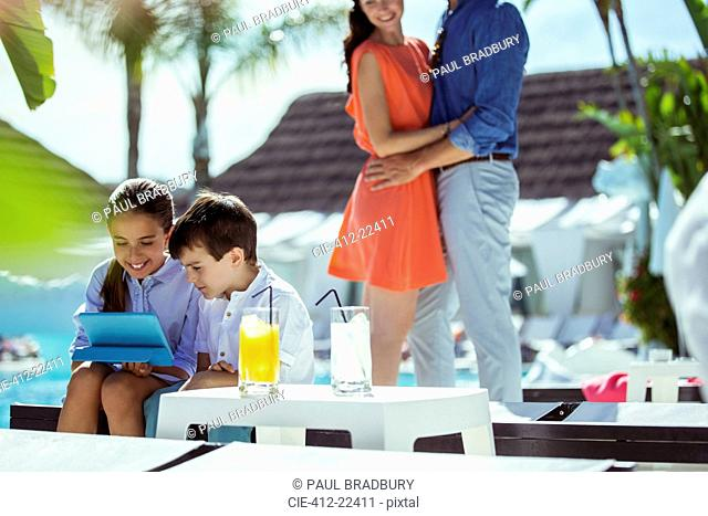 Brother and sister using digital tablet by resort swimming pool, parents embracing in background