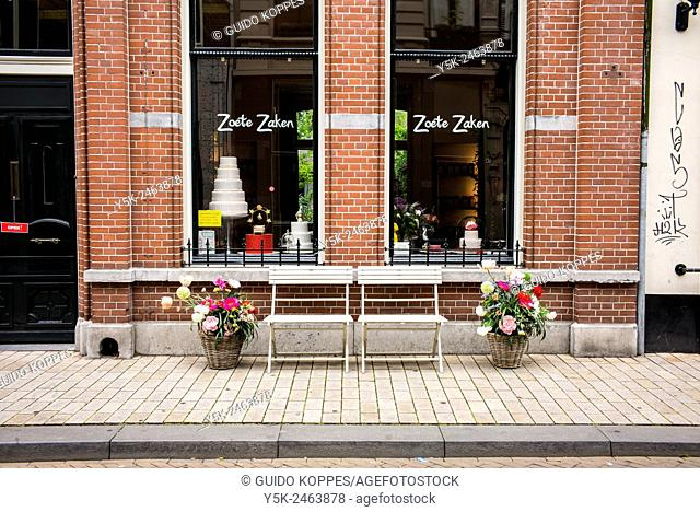 Tilburg, Netherlands. Terrace chairs and pots with flowers in front of the shop windows of 'Zoete Zaken', a pie store in down town Tuinstraat