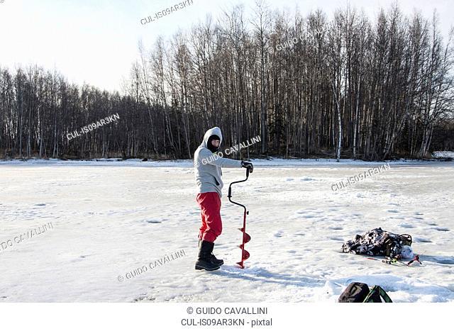 Mid adult man ice drilling, Fairbanks, Alaska