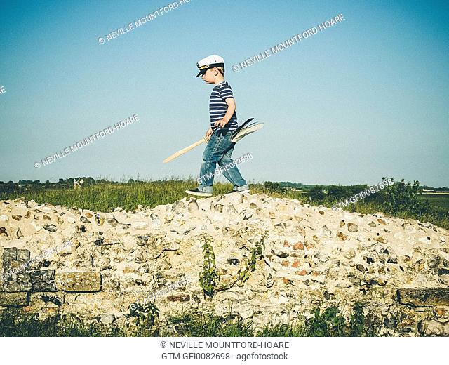 Boy walking on ruined wall