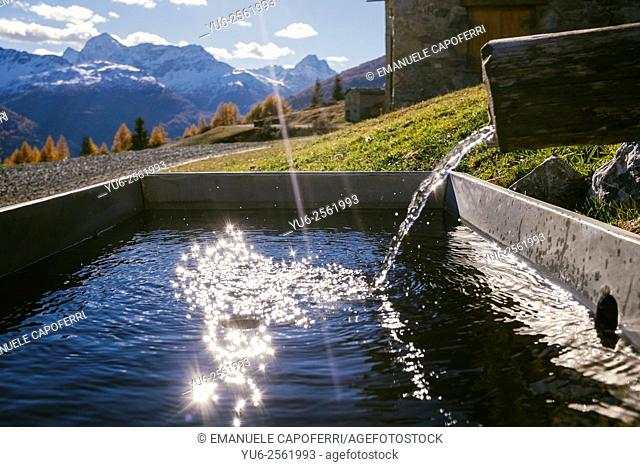 Autumn in the mountains, reflections of the sun on the water of a fountain, Valdidentro, Alta Valtellina, Lombardy, Italy