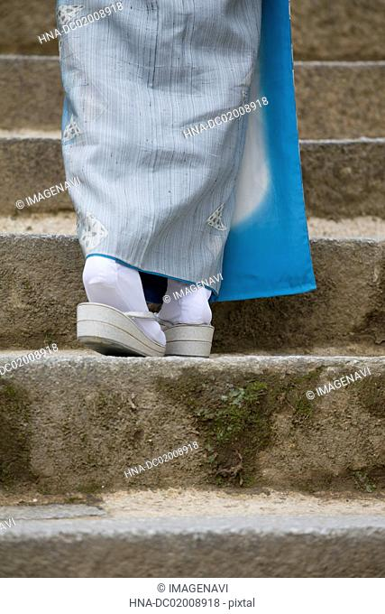 Woman's feet in kimono with Zouri (Japanese sandals) on stone stairs
