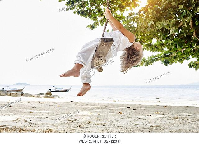 Thailand, Phi Phi Islands, Ko Phi Phi, little girl on a rope swing on the beach