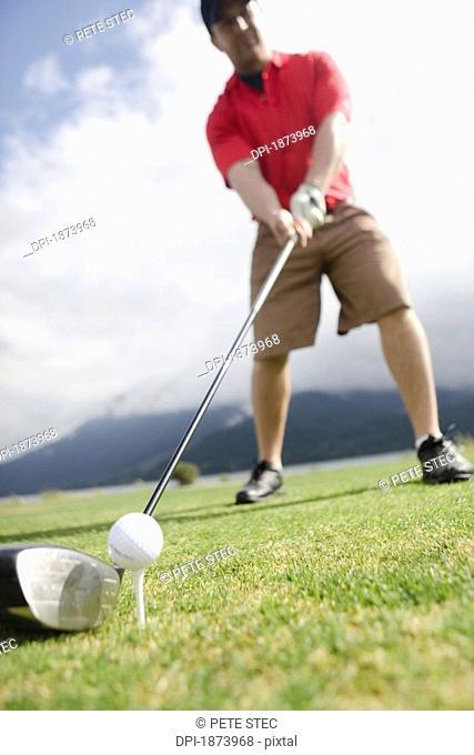 a man ready to hit a golf ball on a tee