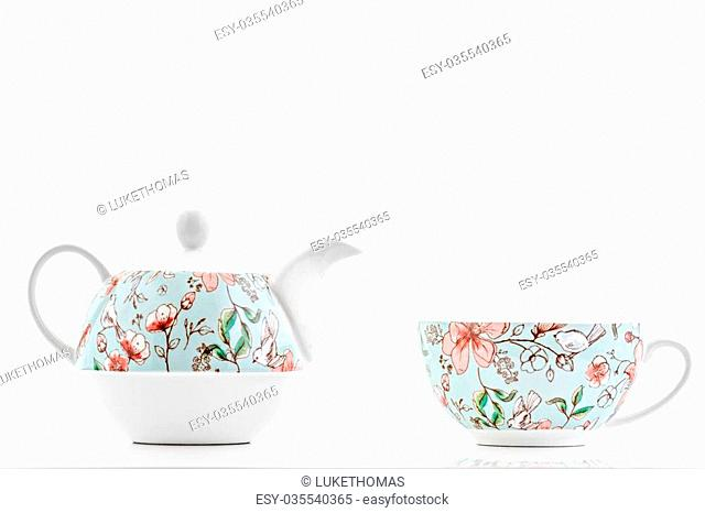 A tea cup and tea pot for one photographed on a white background with a reflction