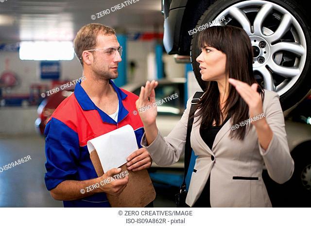 Car mechanic and customer discussing car repair
