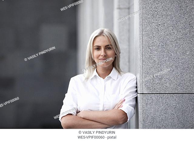 Portait of confident businesswoman leaning against a wall