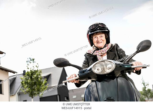 Active senior lady riding motor scooter in the city