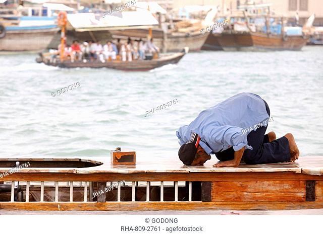 Praying muslim in Dubai harbour, Dubai, United Arab Emirates, Middle East