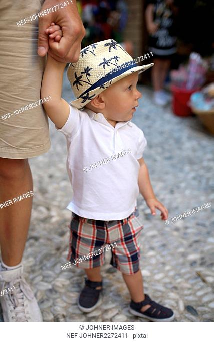 Boy holding fathers hand