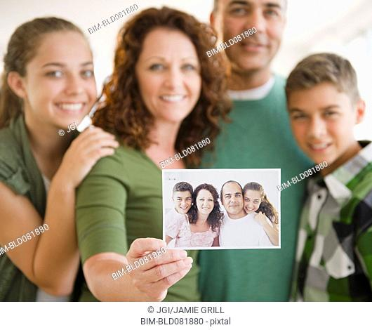 Hispanic woman with family holding out family portrait