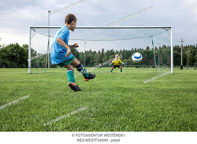 Young football player kicking ball in front of goal with goalkeeper