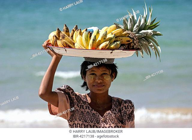 Native woman with a bowl of bananas on her head and Thanaka paste on her face, selling bananas on the beach of Ngapali Beach, Thandwe, Rakhine State, Myanmar