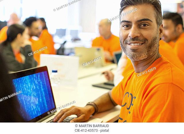 Portrait confident hacker at laptop coding for charity at hackathon