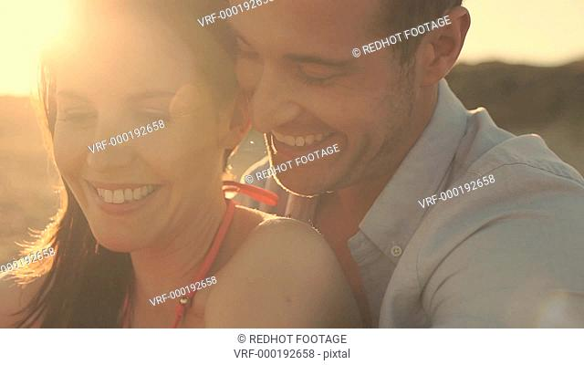 Close up of young couple laughing on beach in sunset