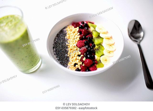 healthy eating, food and diet concept - glass with juice or smoothie and bowl of yogurt with fruits and seeds
