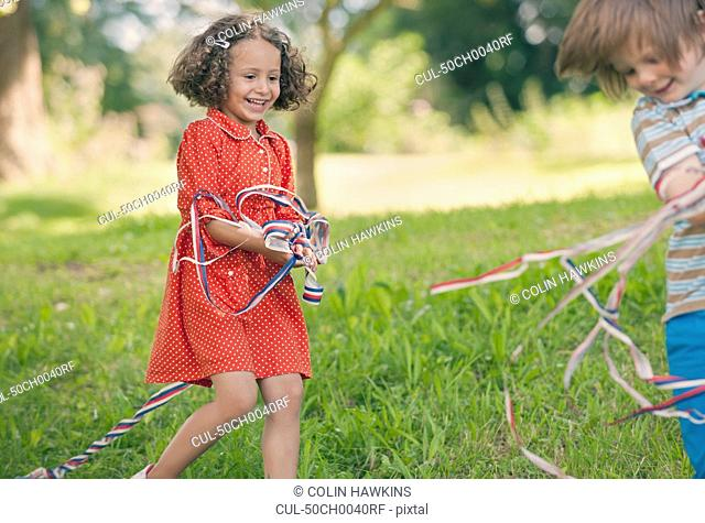 Children playing with ribbons outdoors