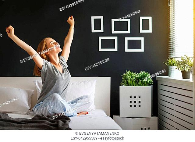 young happy woman woke up in the morning in the bedroom by the window with her back