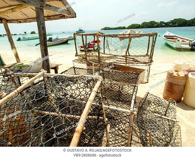Caribbean Seafood market, Panulirus argus, Traps piled on the shore with boats in the background