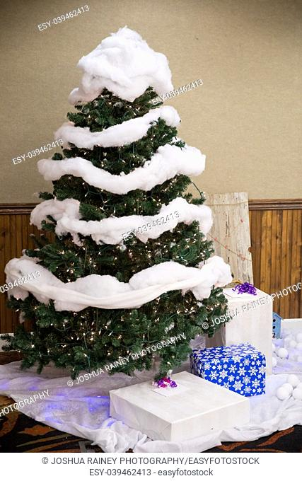Indoor decor at a wedding reception featuring this Christmas tree where guests can leave presents during a winter wedding in Oregon near Christmas time and the...
