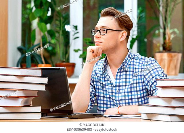 Portrait of a handsome smart student wearing glasses sitting at the table in a library and holding his hand on his chin thinking of something