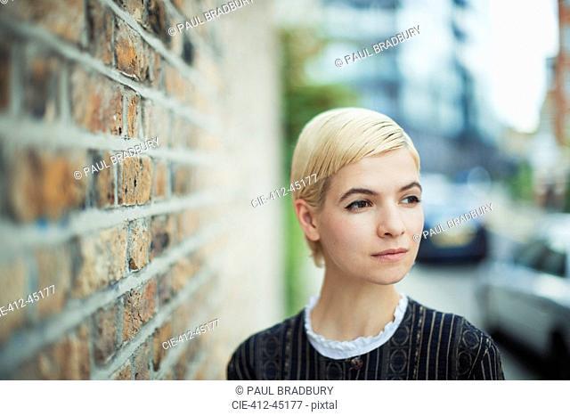 Serene young woman looking away on urban sidewalk