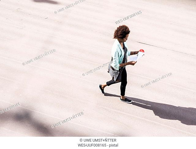 Walking businesswoman looking at document, seen from above