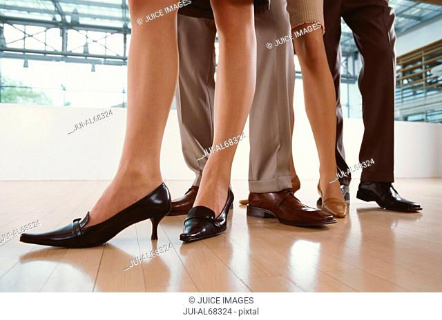 Four executives standing together, focus on their feet