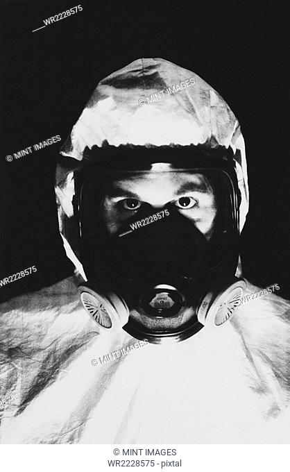 Man wearing a protective clean suit, a suit with head covering and a face mask