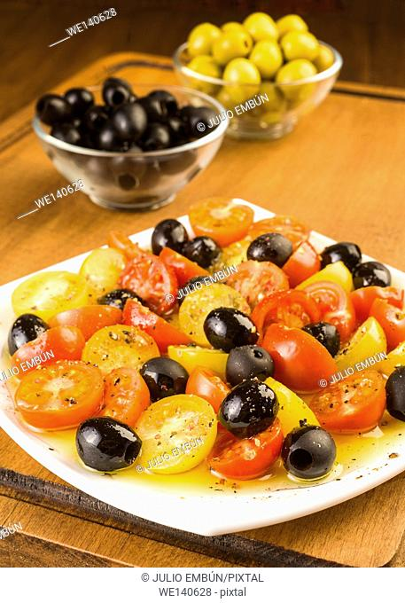 salad with cherry tomatoes and olives on wooden board