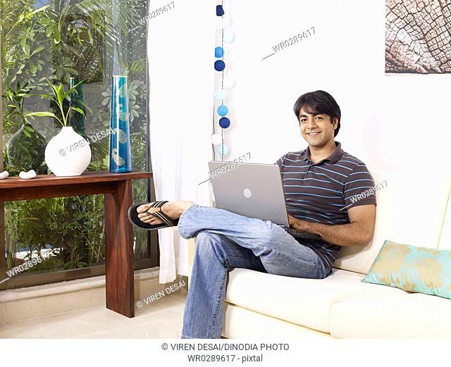 Young man with laptop sitting on sofa MR702V