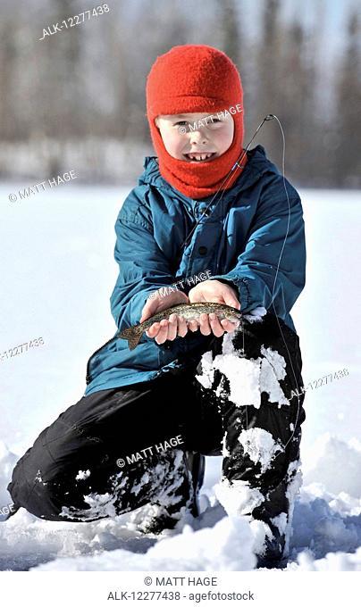 Boy ice fishing on Matanuska Lake in the Matanuska Valley north of Anchorage, Southcentral Alaska