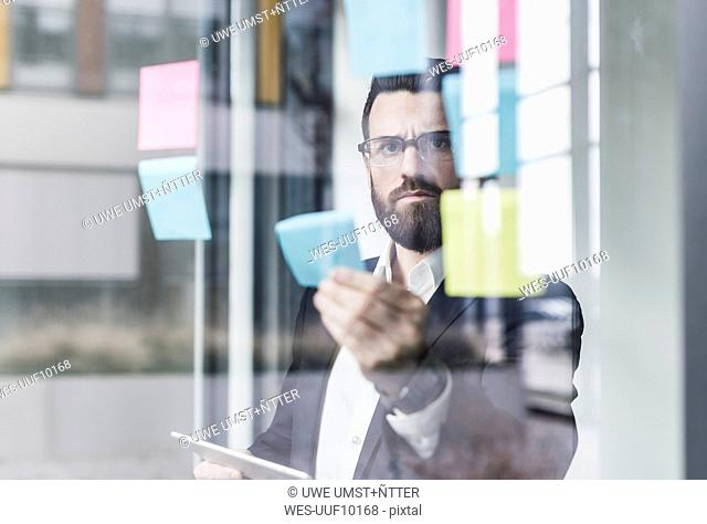 Young businessman attaching adhesive notes to glass pane