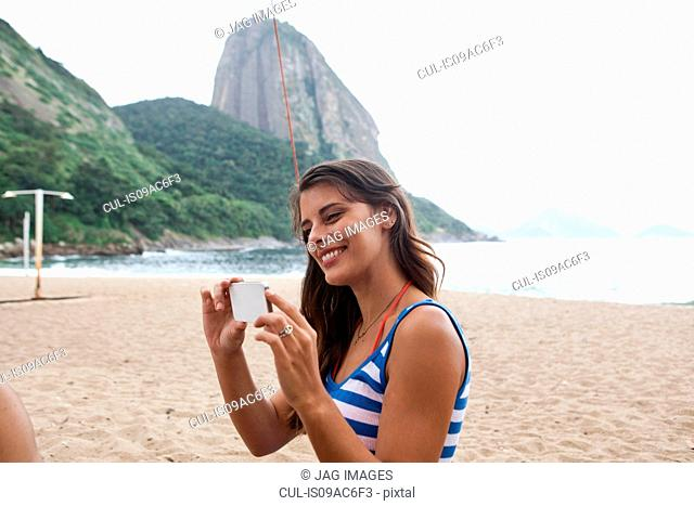 Woman using camera phone on beach, Rio de Janeiro, Brazil