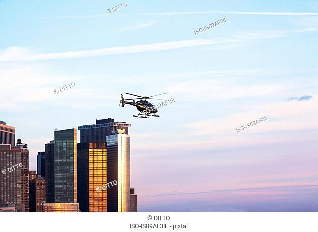 Helicopter and office buildings, New York, USA
