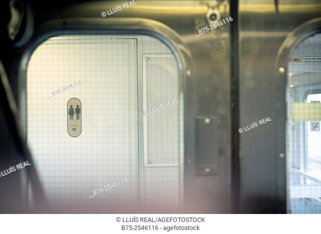 Seen through the window from inside a wagon train to Milan, the door of unisex toilet, WC, within the same train. Italy, Europe