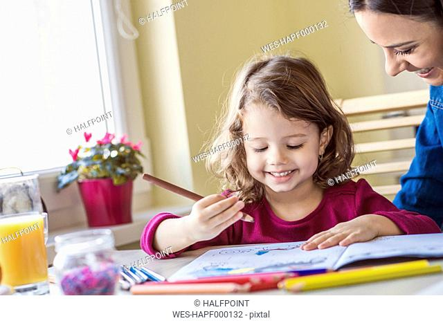Portrait of smiling little girl painting with coloured pencils