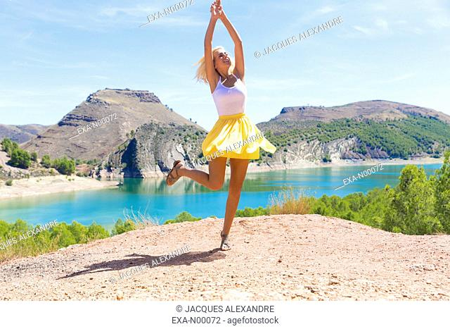 Happy girl with yellow skirt dancing in front of a lake in Aragon, Spain
