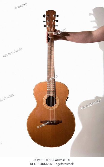 Man holding acoustic Guitar against white background, Munich, Germany