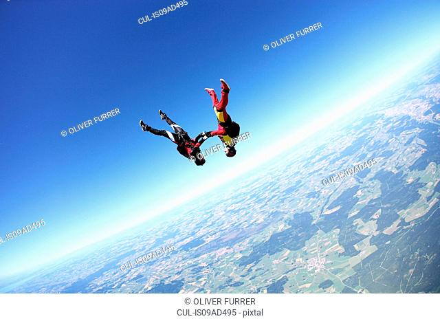 Female skydivers upside down above Leutkirch, Bavaria, Germany