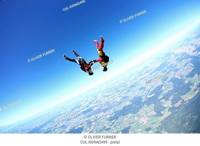 Female skydivers upside down above Leutkirch, Bavaria, Germany