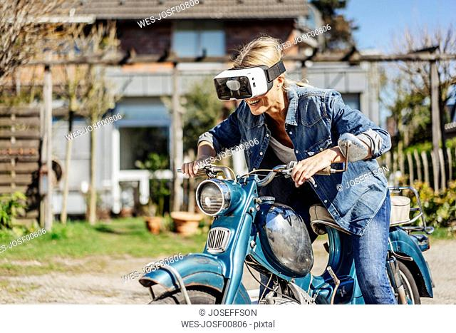 Happy woman on vintage motorcycle wearing VR glasses