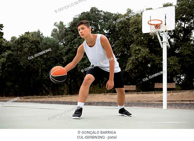 Male teenage basketball player playing basketball on court